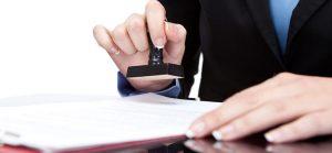 Mężczyzna przybija pieczątkę na dokumencie